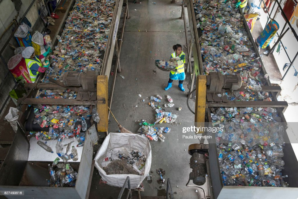 A worker at the Indorama Ventures plastic recycling factory sweeps up bottles that have fallen off a conveyor belt where plastic bottles for recycling are moved into the factory for processing on August 4 ,2017 in Nakon Pathom, Thailand. Indorama Ventures has 70 operating sites in 24 countries. In one year they estimate that they recycle 1.43 billion plastic bottles manufacturing the plastic into Polyethylene Terephthalate (PET) bottle flakes and post consumer recycle (PCR) for the textile market IPI -NPT chips are produced. According to a recent study published, Thailand along with China, Indonesia, the Philippines and Vietnam are on the list of the world's top-five plastic polluters. Cleaning up plastic pollution in Thailand is a challenge due to obstacles caused by culture, infrastructure and environment. Many plastic items like shopping bags, and food wrapping tend to be used for short periods before being discarded.