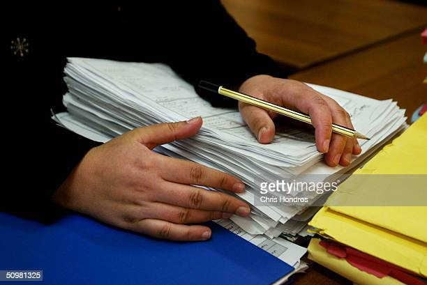 A worker at the Labour ministry holds a stack of resumes on June 21 2004 at the Ministry of Labour in Baghdad Iraq The Labour Ministry has taken...