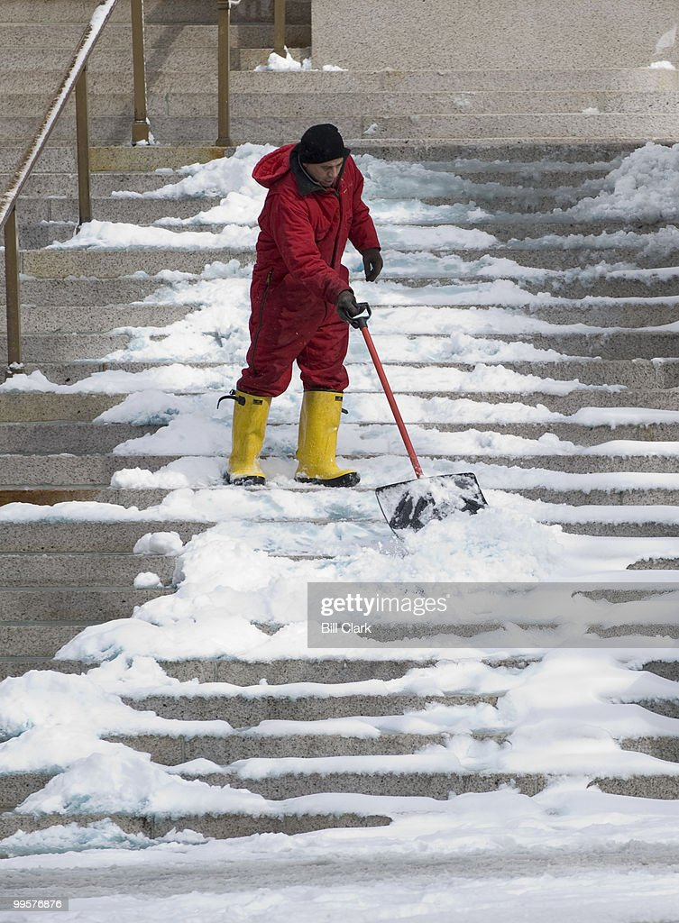A worker at the National Postal Museum building shovels snow off the steps on Monday morning, March 2, 2009.
