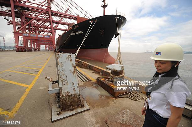 Worker at the Ningbo Port stands beside a container ship wating to be loaded in Ningbo on June 21, 2012. China's manufacturing activity hit a...