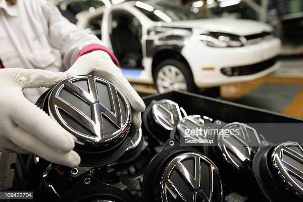 A worker at the photographer's request holds the rear hood ornament showing the VW logo on the assembly line producing new Volkswagen Golf 6 cars at...