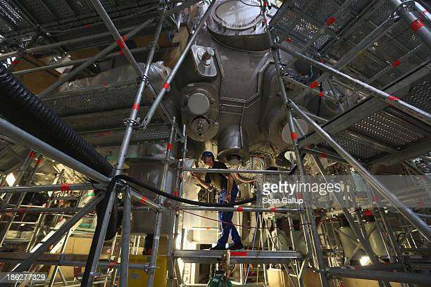 Worker, at the photographer's request, walks on scaffolding under the Wendelstein 7-X experimental fusion reactor at the Max Planck Institute for...