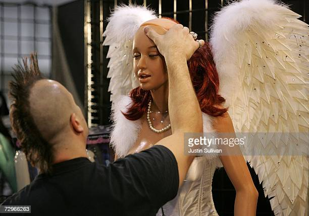 A worker at the Real Doll booth adjusts the face on a silicone sex doll during the 2007 AVN Adult Entertainment Expo at the Sands Convention Center...