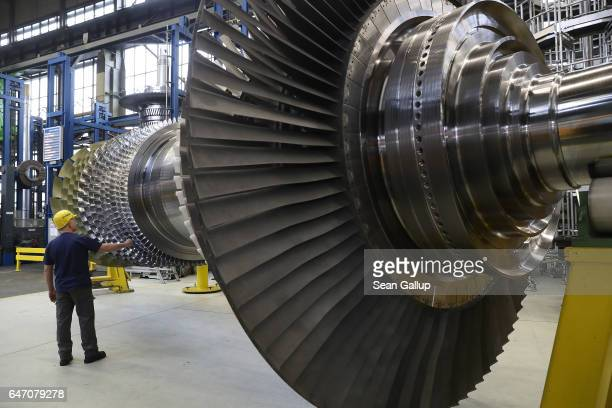 A worker at the request of members of the media who were present touches a turbine at the Siemens gas turbine factory on March 2 2017 in Berlin...