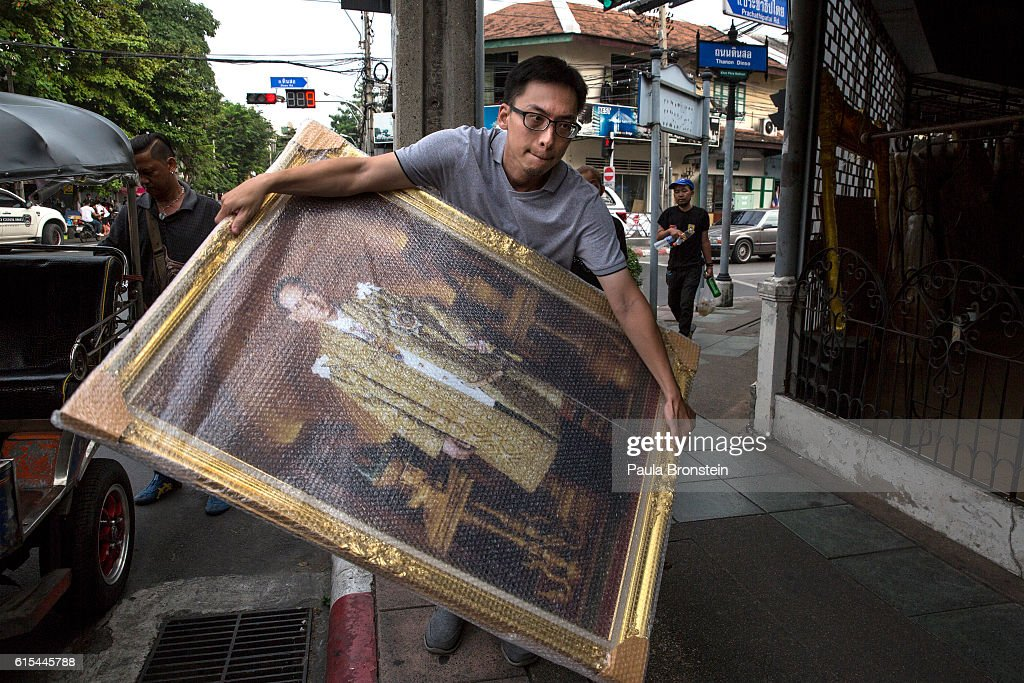A worker at the Sreewanchat shop that specializes in monarchy collections moves large paintings as sales have increased with the demand for Thai King memorabilia on October 18, 2016 in Bangkok, Thailand. Thailand's King Bhumibol Adulyadej, the world's longest-reigning monarch, died at the age of 88 in Bangkok's Siriraj Hospital on Thursday after his 70-year reign. The Crown Prince Maha Vajiralongkorn had asked for time to grieve the loss of his father before becoming the next king as nation waits for the coronation date.