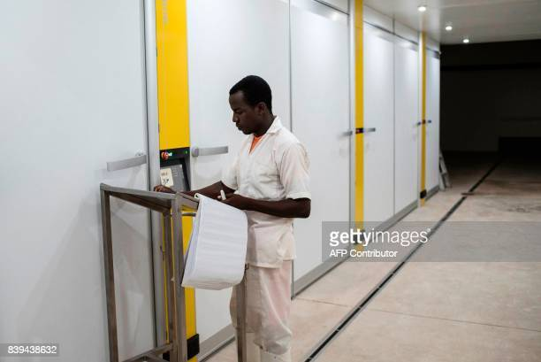A worker at the Valentine Chicken Hatchery monitors and logs the temperatures of the incubation rooms on July 11 2017 Farming in Nigeria is not for...