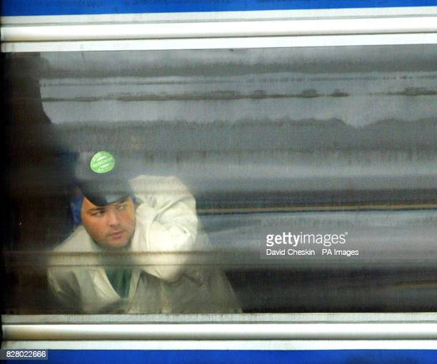 A worker at the Wiseman dairies East Kilbride looks on at farmers as they block the main gate in protest Scottish dairy farmers are blockading milk...