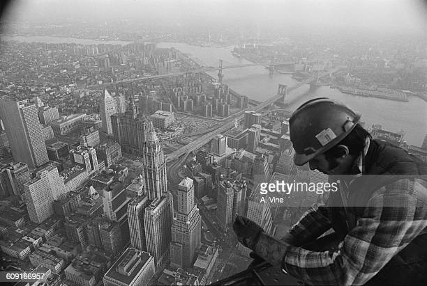 A worker atop the World Trade Center during its construction in New York City USA 1971 The Woolworth Building Brooklyn Bridge and Manhattan Bridge...