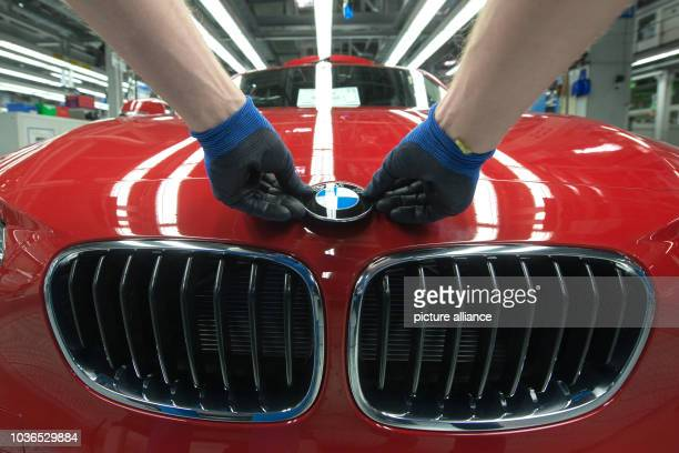 A worker attaches a BMW logo onto the bonnet of a red BMW series 1 car model in the assembly plant of car manufacturer BMW in Regensburg Germany 13...