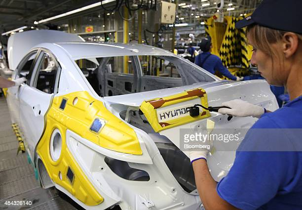 A worker attaches a Hyundai badge to the trunk of a Hyundai Solaris vehicle on the production line at the Hyundai Motors Corp automobile plant in St...
