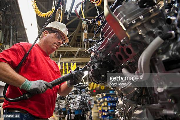 a worker attaches components to an auto engine - indiana stock pictures, royalty-free photos & images