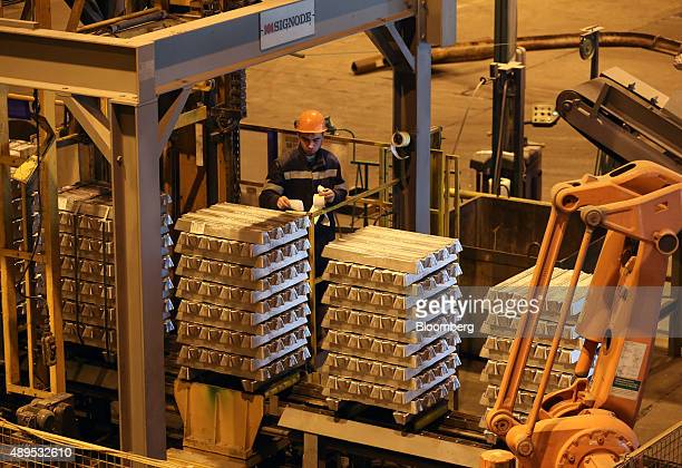 A worker attaches labels to stacks of aluminum ingots in the foundry at the Irkutsk aluminium smelting plant operated by United Co Rusal in Shelekhov...