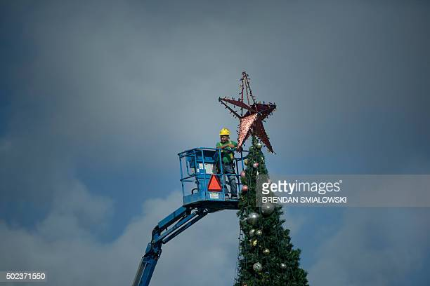 A worker attaching a star on a Christmas tree watches as a motorcade with US President Barack Obama leaves the Marine Corps Base Hawaii on December...