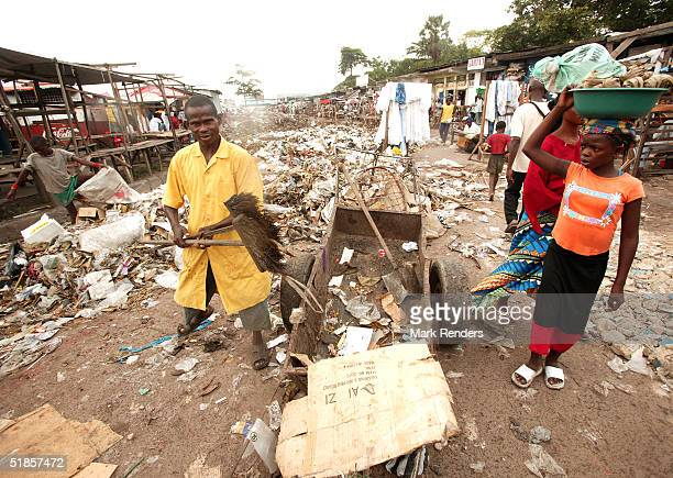 A worker attempts to clean the filthy streets at the Central Market in Kinshasa on December 13 2004 in Democratic Republic of Congo A government...