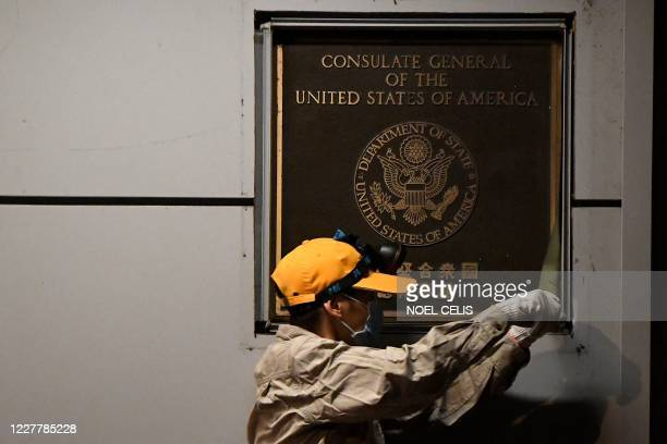 Worker attempts to remove the wall insignia of the US Consulate in Chengdu, southwestern China's Sichuan province, on July 26, 2020. - Workers...