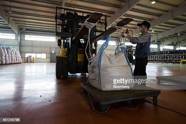 A worker attends a bag of ferrochrome an ingredient used to make stainless steel on a forklift truck at the Korea Resource Corp warehouse in Gunsan...