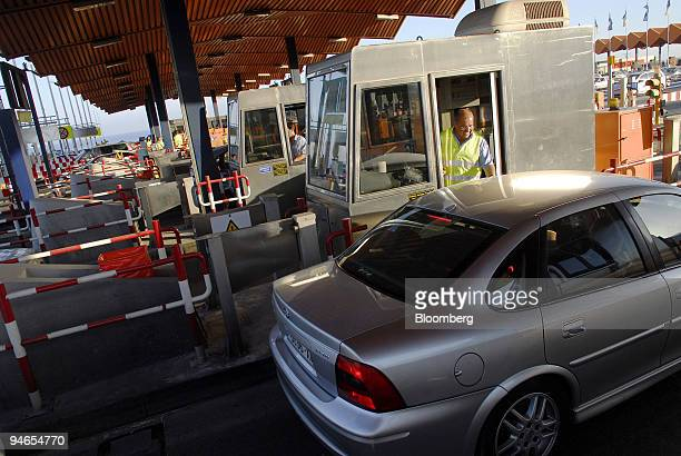 A worker attends to a motorist at a highway toll operated by Acesa Infraestructuras a subsidiary company of Abertis in Vilassar de Mar Spain on...