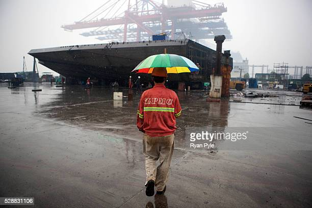 A worker avoids heavy rain with an umbrella at ZPMC Shanghai Zhenhua Heavy Industry In the background is one of the few remaining sections of the...