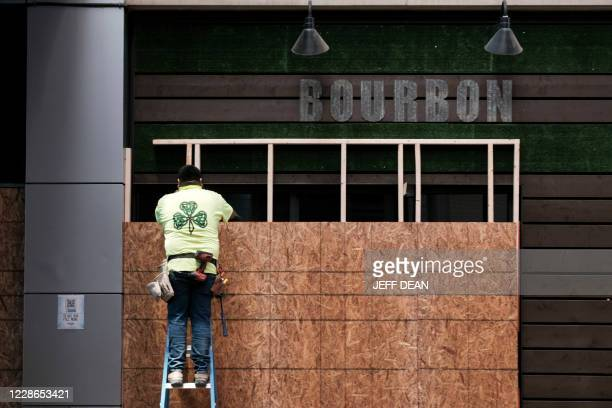 Worker boards up a business in downtown Louisville, Kentucky on September 22, 2020 in anticipation of the results of a grand jury inquiry into the...