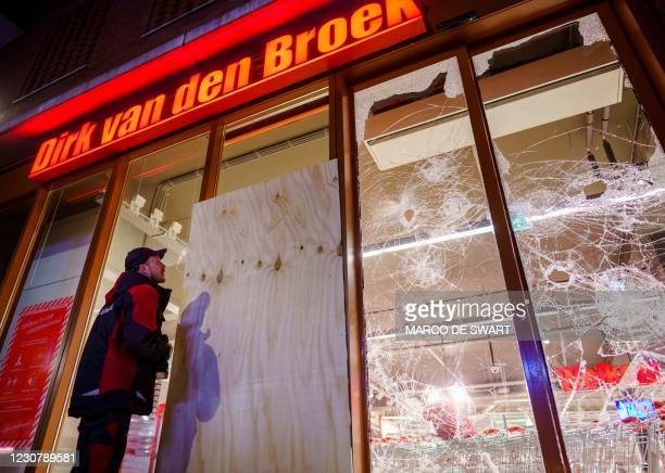 Worker boards up broken windows on a branch of supermarket chain Dirk van den Broek in Rotterdam, on January 25 after a second wave of riots in the...