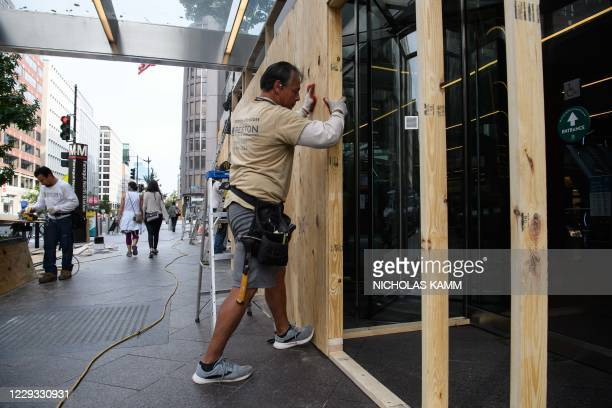 Worker boards up the entrance of an office building in Washington, DC, on October 28 six days before the US presidential election, as businesses fear...