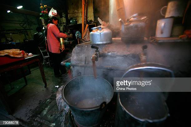 Worker boils water at a Laohuzao teahouse at an alleyway January 23, 2007 in Shanghai, China. Laohuzao is a traditional store which sells hot water...