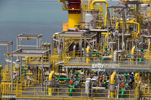 A worker bottom right walks on the Tullow Oil Plc Prof John Evans Atta Mills Floating Production Storage and Offloading vessel docked at the Sembcorp...