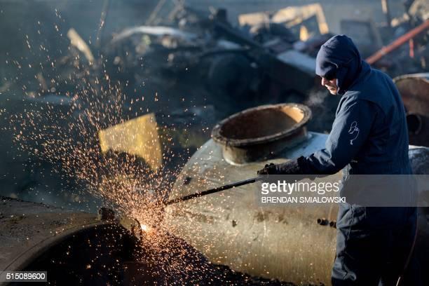A worker breaks down a metal tank at a scrap yard March 12 2016 in Cleveland Ohio / AFP / Brendan Smialowski