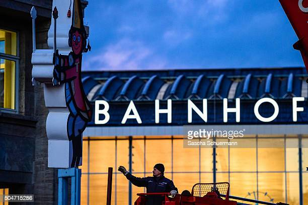 A worker brings carnival decoration on in front of Hauptbahnhof main railway station stands near Hauptbahnhof main railway station where on New...