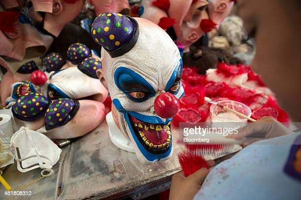 Worker brushes a piece of fake hair before adding it to a latex mask during the production process at the REV Group factory in Morelos, Mexico, on...