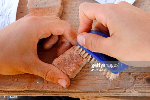 A worker brushes a pottery fragment unearthed at the archaeological site of En Esur where a 5000yearold city was uncovered near the Israeli town of...