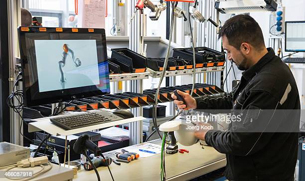 Worker builds a robotic arm at the KUKA industrial robotics factory on March 13 2015 in Augsburg Germany Germany's exportdriven economy has fared...