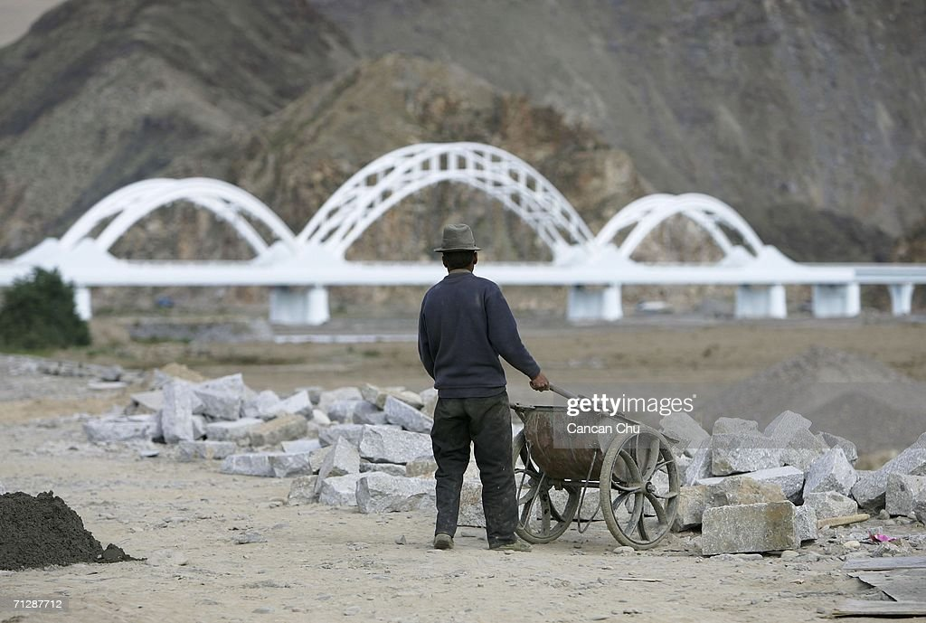 A worker builds the bank of the Lhasa River near a railroad bridge of the Qinghai-Tibet Railway in the shape of Hada (or Khatag), a white scarf that Tibetan people use to express their best wishes, on June 24, 2006 in Lhasa, Tibetan Autonomous Region, China. The Qinghai-Tibet railway will begin trial operations on July 1 and has scheduled the first five trains to Tibet via the new railway, an official with the Qinghai-Tibet Railway Company said. The 1,956-kilometer-long (about 1,215 miles) Qinghai-Tibet railway that links Xining, the capital of Qinghai Province, with Lhasa, capital of Tibet Autonomous Region is the world's highest and longest plateau railroad and also the first railway connecting Tibet with other parts of China. Some 960 kilometers (576 miles) of its track are located 4,000 meters (13,120 feet) above sea level and the highest point is 5,072 meters (16,636 feet), according to state media.