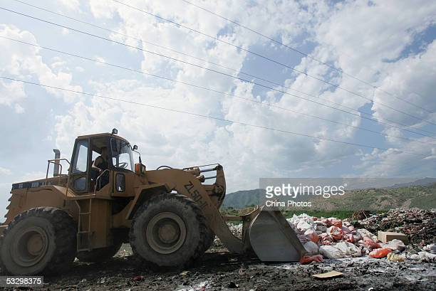 Worker buries disinfected spoiled pork at a dump on July 28, 2005 in Changping County of Beijing, China. Beijing Health Supervision Institute has...