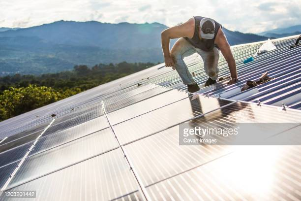 worker carefully works to secure solar panels on roof of building. - 率先 ストックフォトと画像