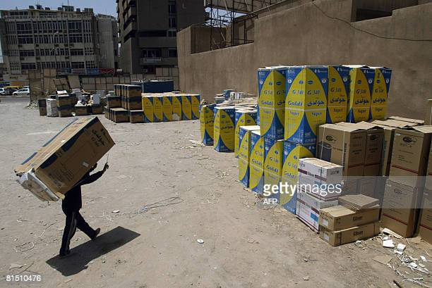 A worker caries a fridge on his back at a depot in the Karada district of Baghdad on June 10 2008 The depot owned by a business man is protected by...