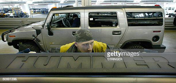 A worker caries a logo of a US automaker in front of a vehicle at the automobile plant in Kaliningrad 24 June 2004 A Russian factory in the Baltic...