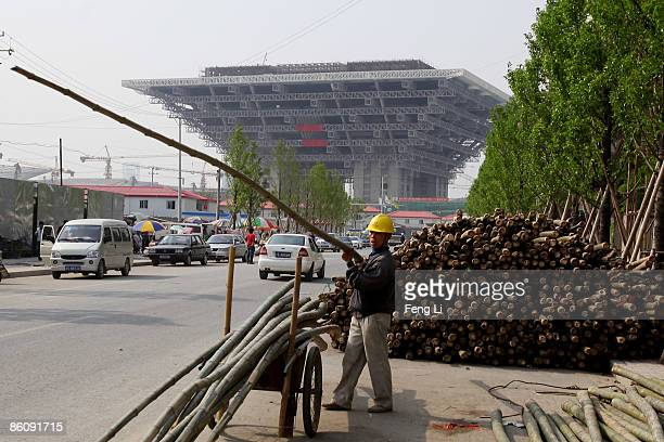 A worker carried the bamboo for repairing peripheral residents' houses in front of the construction of the China Pavilion at the World Expo site on...