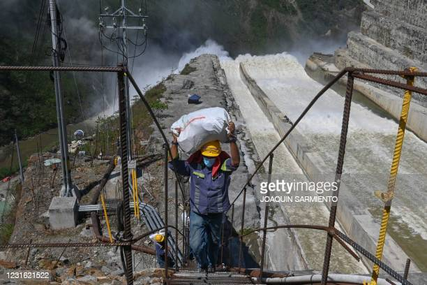 Worker carries a bag near the spillway of the Hidroituango Hydroelectric Project as construction of the dam continues, near the municipality of...