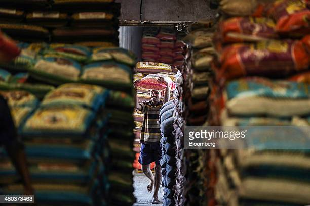 A worker carries a bag of basmati rice on his head into a warehouse in the Vashi Agricultural Produce Market Committee wholesale market in Mumbai...