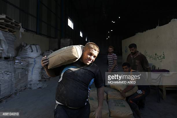 A worker carries a bag of cement at a distrubtion center for Gazans whose houses were destroyed during the 50 days of conflict between Israel and...