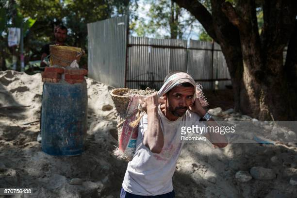 A worker carries a basket of sand on his back at a construction site in the Kirtipur area of Kathmandu Nepal on Wednesday Nov 1 2017 India and China...