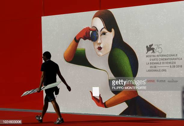 TOPSHOT A worker carries a board as he sets up the red carpet area near the entrance of a screening room ahead of the 75th Venice Film Festival at...