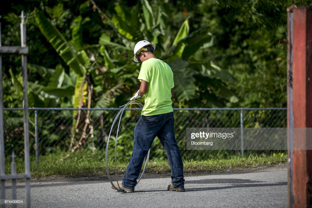 A worker carries a cable while fixing power lines in the town of Limones, Yabucoa, Puerto Rico, on Friday, May 18, 2018. The bankrupt U.S. commonwealth's investment bankers last week started sounding out suitors for the eight-decade-old monopoly known asPrepa, whose rickety infrastructure was almost erased by Hurricane Maria in 2017. The halting efforts to repair the damage and improve the antiquated grid have been the central obstacle in recovery. Photographer: Xavier Garcia/Bloomberg via Getty Images