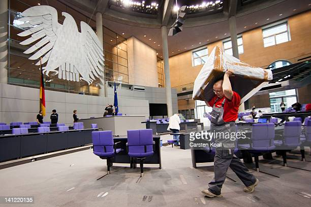 A worker carries a chair in the plenary hall of the Bundestag ahead of the upcoming gathering of the Federal Assembly on March 13 2012 in Berlin...