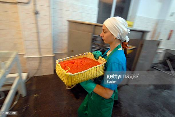 A worker carries a container of salmon caviar at the fish processing plant of the 'People of the North' collective farm on July 28 2007 in the town...