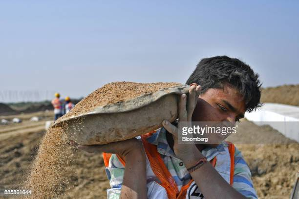 A worker carries a container of sand on his shoulder at an under construction sewerage system on the project site for a 920squarekilometer industrial...