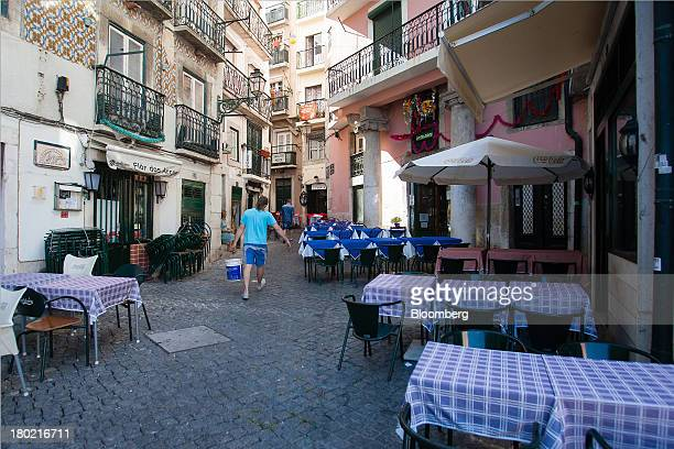 A worker carries a container past empty restaurant tables on a side street in the Alfama quarter of Lisbon Portugal on Monday Sept 9 2013 Prime...