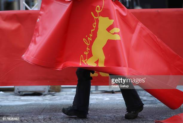 A worker carries a cover with the Berlinale bear logo during preparations outside the Berlinale Palace prior to the 68th Berlinale International Film...
