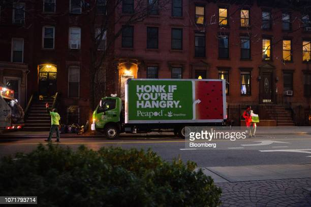 A worker carries a crate of groceries during a Peapod delivery at sunrise in the Brooklyn borough of New York US on Monday Dec 10 2018 With almost 9...
